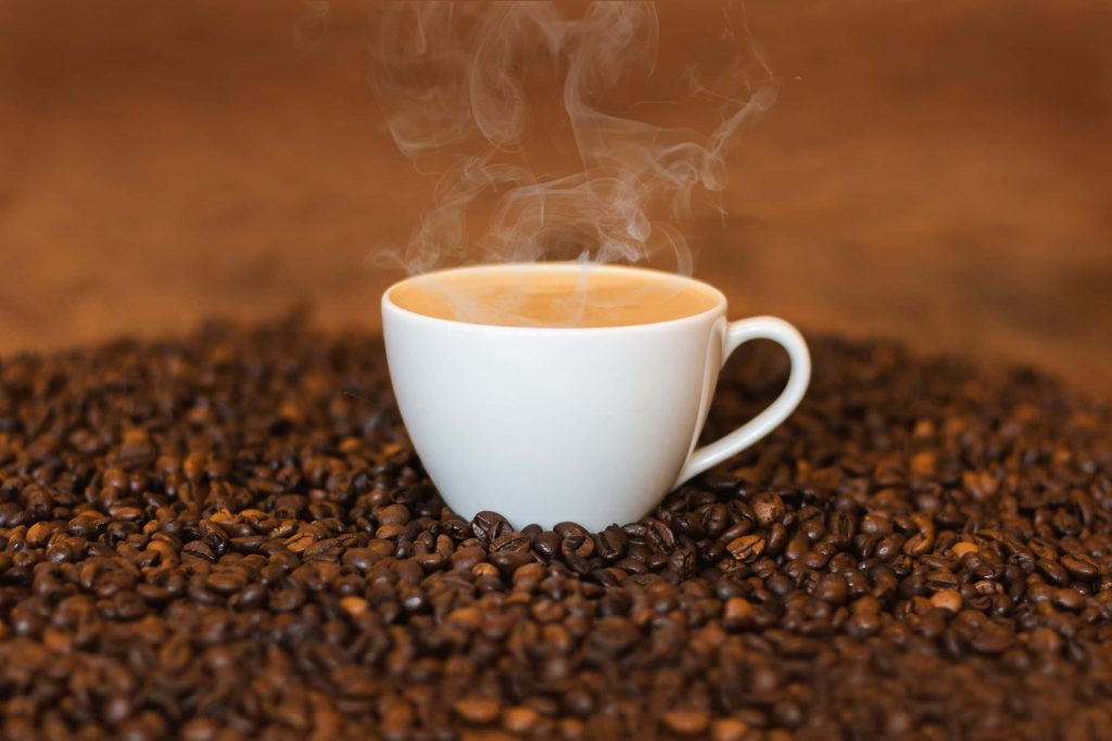 A cup of office coffee on a bed of coffee beans