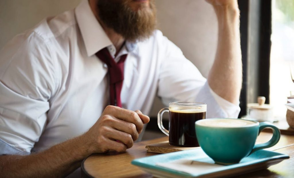 Man drinking coffee form an Office Coffee Machine
